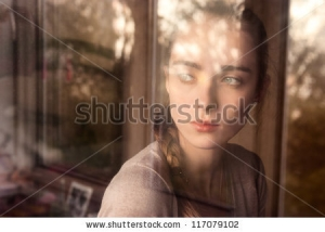 stock-photo-beautiful-girl-standing-at-the-window-watching-117079102