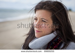 stock-photo-thoughtful-pretty-woman-at-beach-looking-out-to-sea-89800255